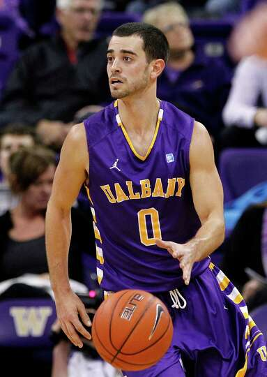 Albany's Jacob Iati brings the ball up court against Washington in the first half of an NCAA college