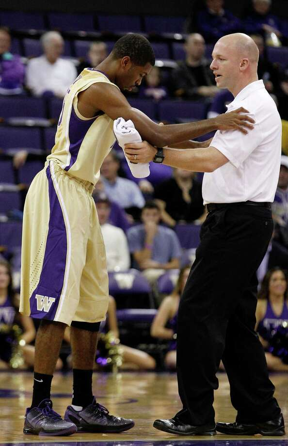 Washington's Scott Suggs, left, is assisted by trainer Pat Jenkins after Suggs took a hit to the head against Albany in the first half during an NCAA college basketball game, Tuesday, Nov. 13, 2012, in Seattle. Suggs left the game and was reported to have suffered a concussion. Photo: Elaine Thompson, AP / AP