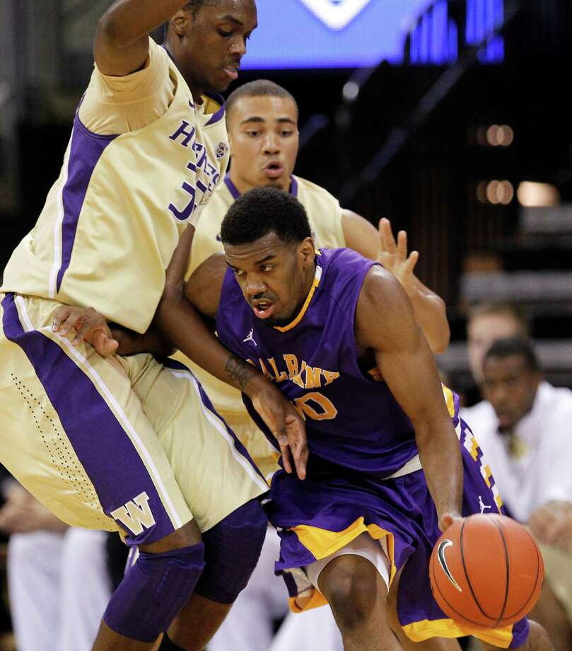 Albany's Jayson Guerrier, right, tries to get past Washington's Jernard Jarreau, left, and Andrew Andrews in the first half of an NCAA college basketball game, Tuesday, Nov. 13, 2012 in Seattle. Photo: Elaine Thompson, AP / AP