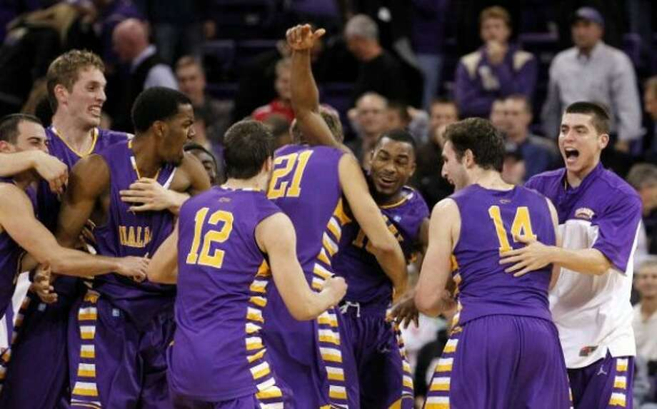Albany's Mike Black, center, raises his arms as he celebrates with teammates after they defeated Washington in an NCAA college basketball game, Tuesday, Nov. 13, 2012, in Seattle. Black hit the winning shot as Albany won 63-62. (AP Photo/Elaine Thompson)