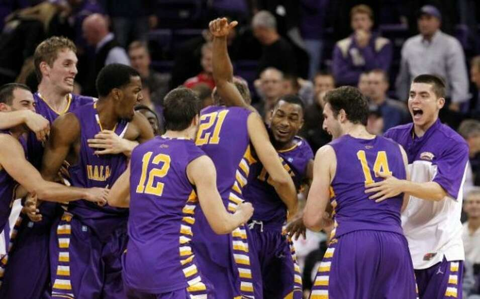 Albany's Mike Black, center, raises his arms as he celebrates with teammates after they defeated Was