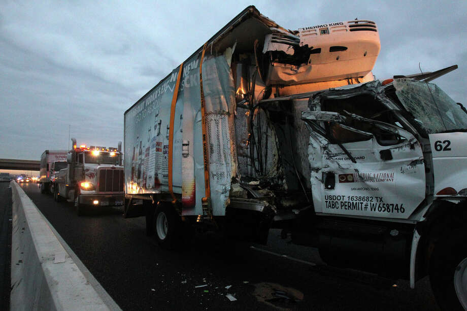 Two large trucks are hauled off by wreckers after a crash took place on IH-35 southbound near Loop 1604 Wednesday November 14, 2012. Live Oak police said the accident took place about 5:25 a.m. after one of the trucks struck a concrete barrier. All lanes on the interstate were closed until 7:00 a.m. . Photo: John Davenport/Express-News