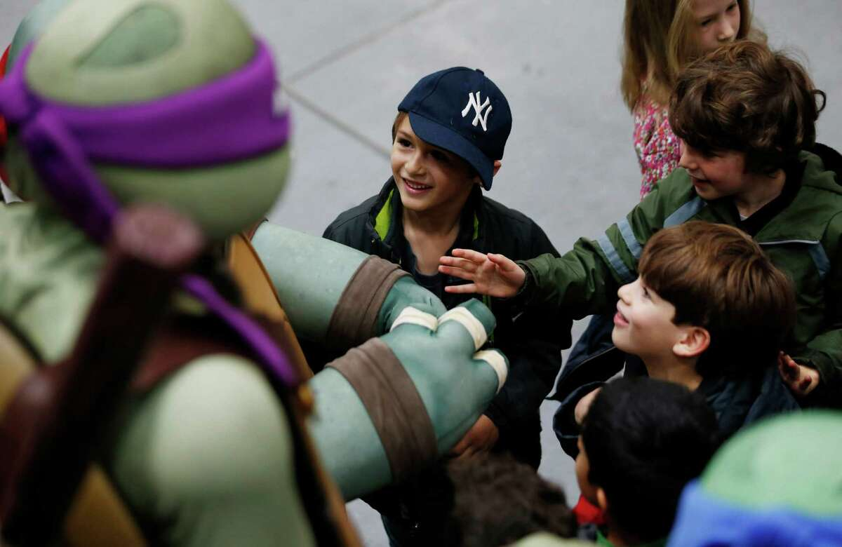 Avi Printz, center, of Hunter College Elementary School, reacts as he and classmates meet the characters the Teenage Mutant Ninja Turtles during a sneak peek of the new floats for the Macy's Thanksgiving Day Parade at Macy's Studio, Tuesday, Nov. 13, 2012, in Moonachie, N.J.