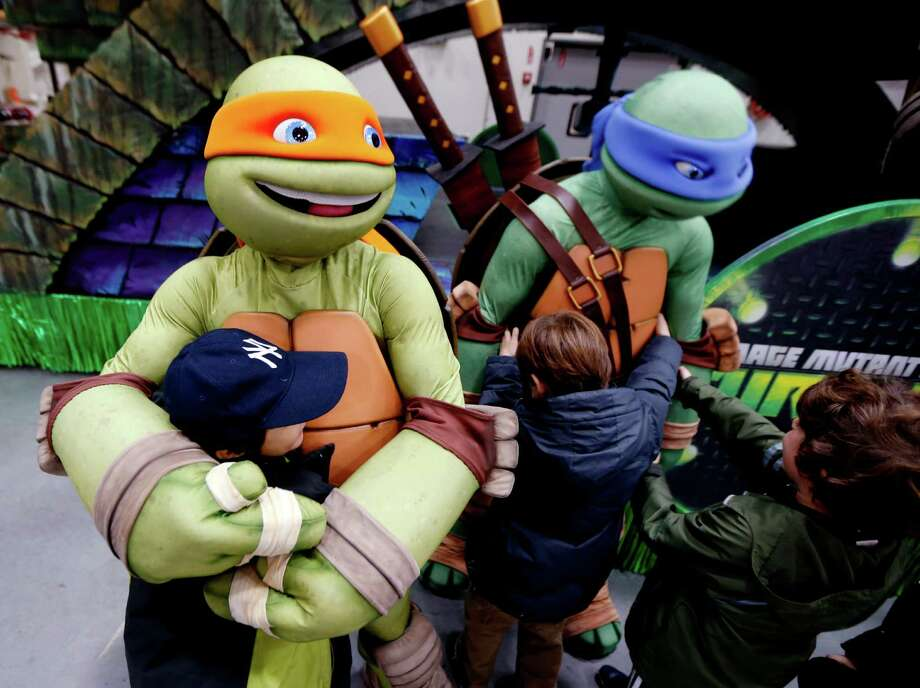 Avi Printz, left, of Hunter College Elementary School, gets a hug from a character of the Teenage Mutant Ninja Turtles during a sneak peek of the new floats for the Macy's Thanksgiving Day Parade at Macy's Studio, Tuesday, Nov. 13, 2012, in Moonachie, N.J. Photo: Julio Cortez, AP / AP