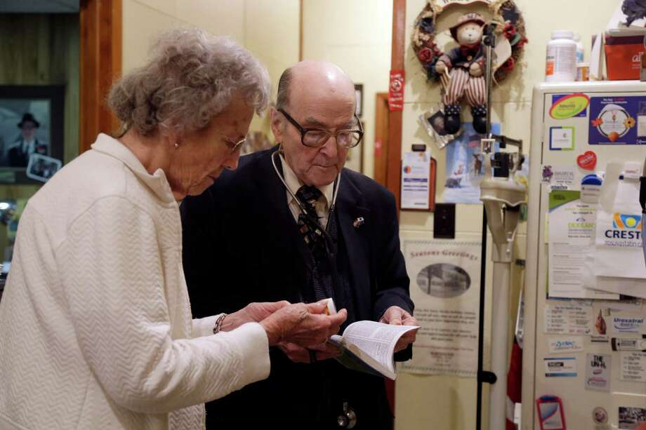 In this Tuesday, Oct. 30, 2012 photo, Dr. Russell Dohner, right, talks with nurse Rose Busby about a patient's prescription in Rushville, Ill. In an era of rising healthcare costs, the 87-year-old doctor only charges patients $5 per office visit and doesn't take insurance saying it isn't worth the bother. Photo: Jeff Roberson, AP / AP