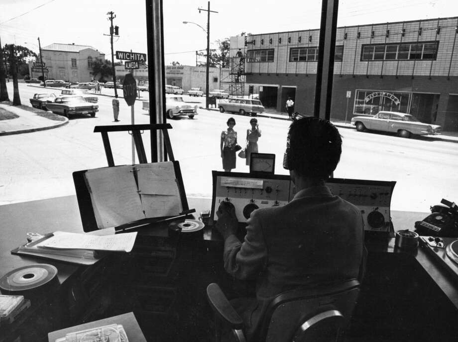 A KCOH disc jockey speaks to listeners driving past. He often invites them in to sample an advertiser's product, 1963. (Houston Post)