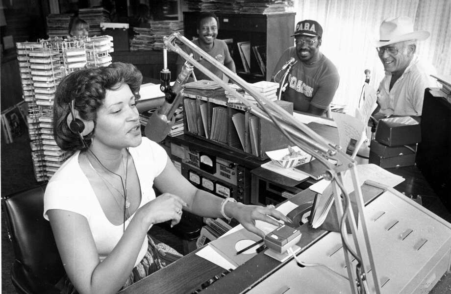 Cassandra Domanguex, a disc jockey at KCOH, accepts pledges on the air during a radiothon to benefit the Progressive Amateur Boxing Association, while, from left, KCOH disc jockey Joe Williams, the Rev. Ray Martin, and former police Chief B.K. Johnson look on. Published Sept. 2, 1982. (Houston Chronicle)