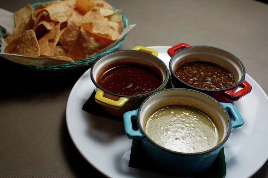 The trio of salsas includes one with tomatillos and peanuts, center; five chiles with five peppers and pork rinds, left, and burnt pepper skin, right. Photo: Johnny Hanson, Staff / © 2012  Houston Chronicle