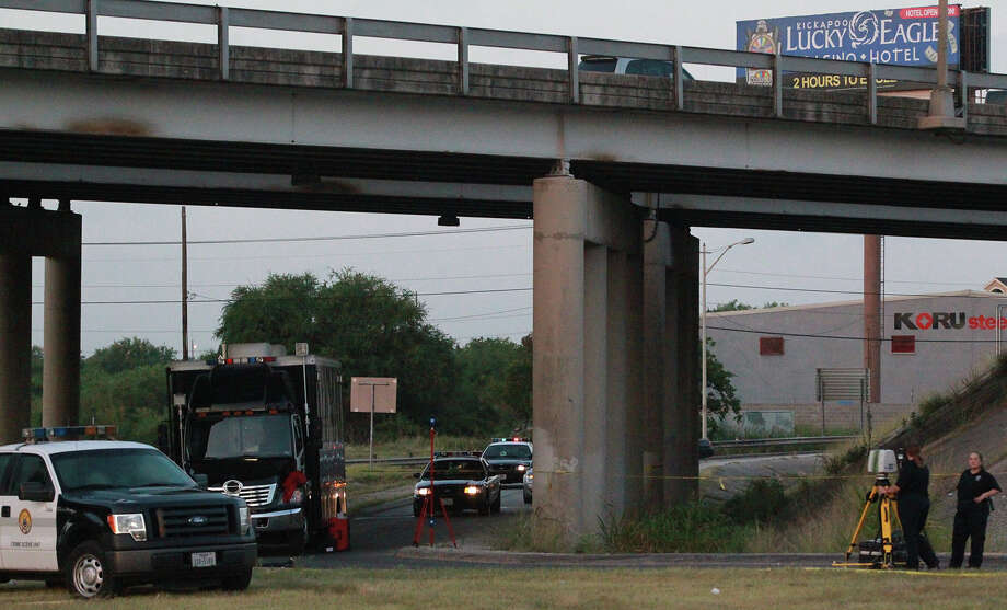 San Antonio police investigate Thursday July 11, 2013 under Interstate highway 35 near the AT&T Parkway exit where the body of a man was found early in the morning in a turnaround lane. Police say the man had been shot and there was a trail of blood on the southbound feeder road. The incident is still being investigated. Photo: JOHN DAVENPORT, SAN ANTONIO EXPRESS-NEWS / ©San Antonio Express-News/Photo may be sold to the public