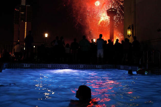Children swim and people watch fireworks from the Hilton Palacio del Rio pool during the Stars & Stripes over San Antonio inaugural event on Wednesday, July 4, 2012. Photo: Lisa Krantz, Express-News/File Photo / San Antonio Express-News