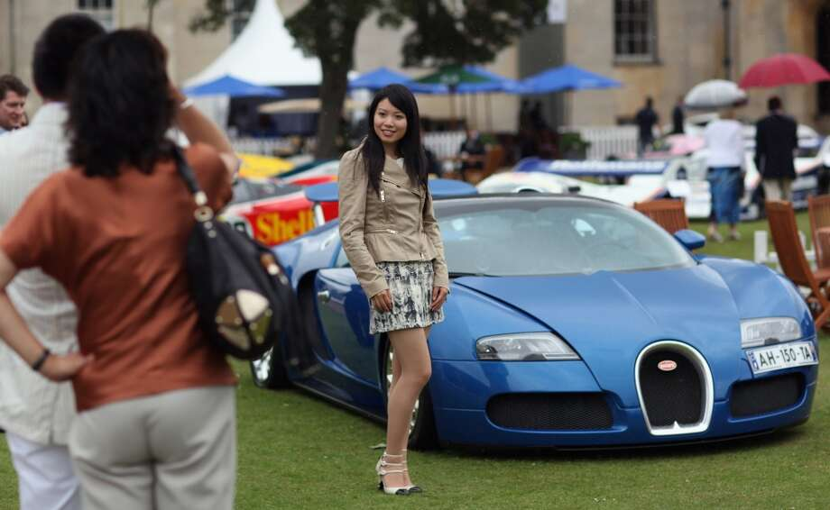 A woman has her photograph taken in front of a Bugatti Veyron at the 'Salon Prive' luxury and supercar event on June 22, 2011 in London, England. The annual three day Salon Prive offers the opportunity to view the most exotic modern and vintage super cars in the world and is being held for the first time at Syon Park. (Dan Kitwood / Getty Images)