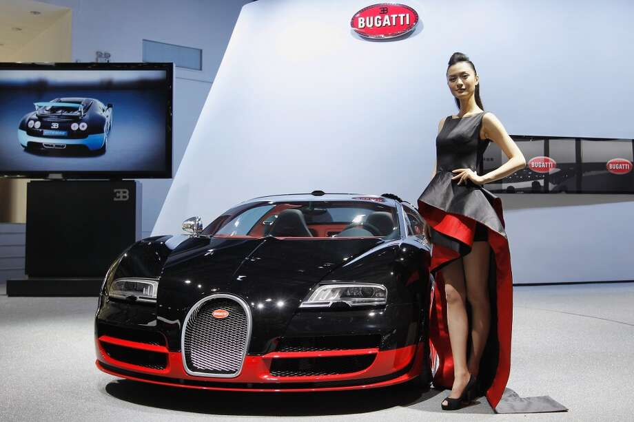 A model stands beside a Bugatti during the media day of the 2012 Beijing International Automotive Exhibition at Beijing International Exhibition Center on April 23, 2012. (Getty Images)