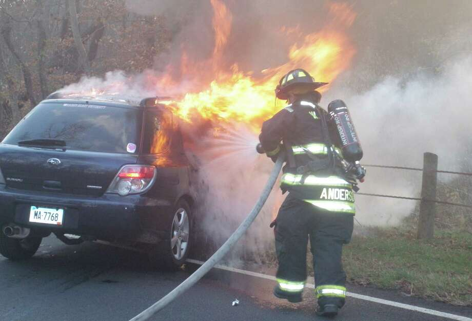 A firefighter battles flames that engulted a car involved in a multi-vehicle crash Wednesday on the Merritt Parkway, which several drivers said was caused after they struck a coyote on the highway.   Westport CT 11/14/12 Photo: Westport Fire Department / Westport News contributed