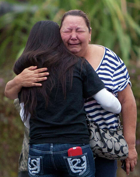 Friends and family cry at a scene after a a man was fatally shot and another wounded Wednesday, Nov.