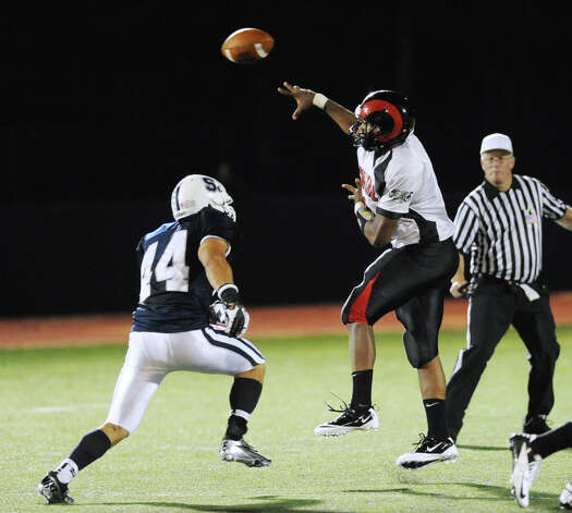 Bridgeport Central quarterback Xavier Hardison throws while being pressured by Pieter Hoets, left,  # 44 of Staples, during Hhigh school football game between Staples High School and Bridgeport Central High School at Staples in Westport, Friday night, Sept. 21, 2012. Photo: Bob Luckey / Greenwich Time