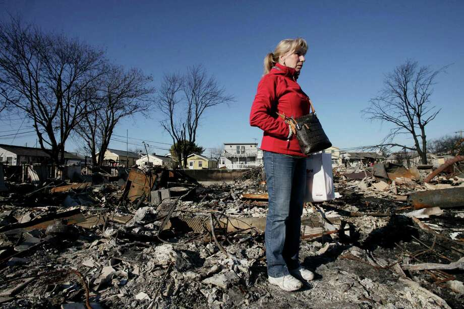 Cathy O'Hanlon poses in front of the charred remains of her home in the Breezy Point section of the Queens borough of New York, Wednesday, Nov. 14, 2012. A fire destroyed more than 50 homes in the oceanfront community during Superstorm Sandy. O'Hanlon and her husband plan to rebuild the house. (AP Photo/Mark Lennihan) Photo: Mark Lennihan, STF / AP