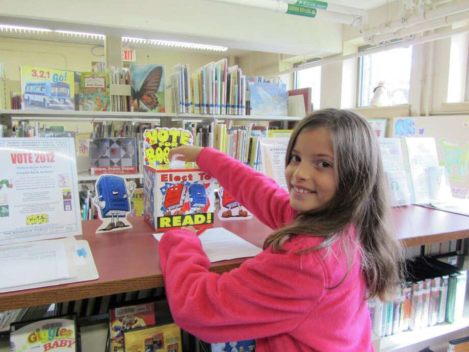Peyton Korzenik, a fifth grader at Brookside Elementary School, votes for her favorite author at the South Norwalk Libary. Photo: Contributed Photo