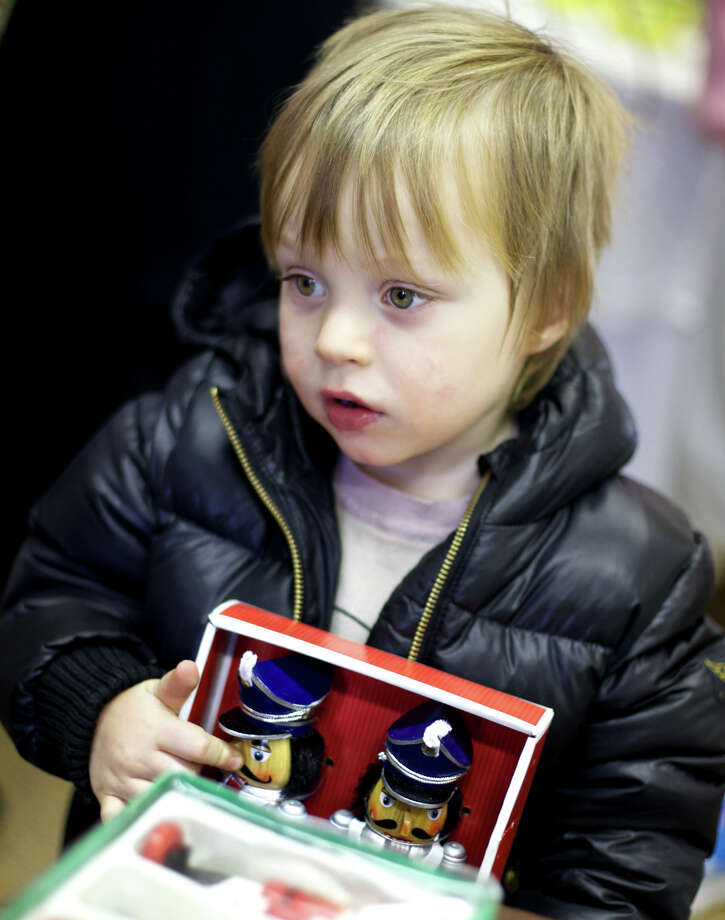 "Archie Harrison, 3, of Washington borrows some family dollars to purchase nutcrackers because he wanted to play with them ""right now"" during the Women's guild's holiday bazaar at Our Lady of Perpetual Help Church in Washington. Nov. 10, 2012 Photo: Trish Haldin"