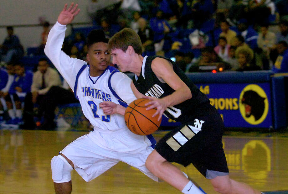 Nederland's Zach English controls the ball as Ozen's Jakobi Jones guards at Ozen High School in Beaumont, Friday, February 10, 2012. Tammy McKinley/The Enterprise Photo: TAMMY MCKINLEY