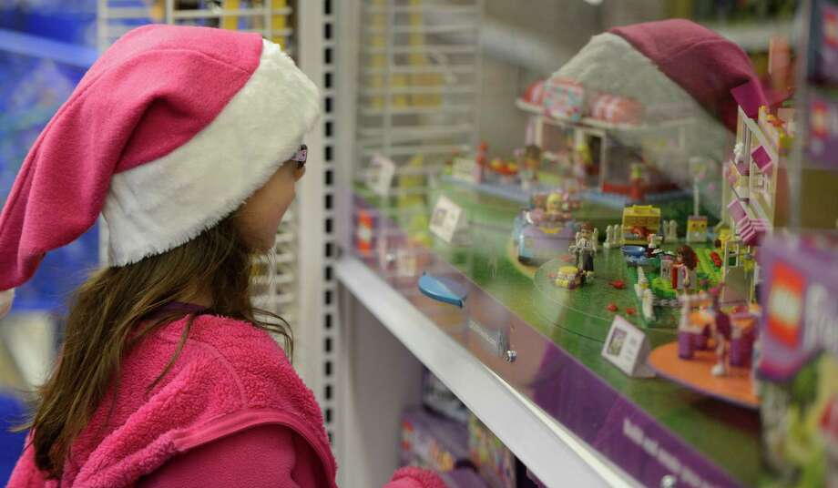 "Leandra Prudencio, 6, of Colonie looks over some of the toys at the Toys R Us store in Colonie, N.Y., as she and her mother, Gina, gathered toys for the Marine Corps League ""Toys for Tots"" program sponsored by Dunkin' Donuts on Nov. 14, 2012.  The purchase of the toys for the Toys for Tots program was made possible by a donation of $25,000 from Dunkin' Donuts.   (Skip Dickstein/Times Union) Photo: Skip Dickstein / 00020134A"
