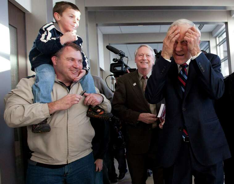 Ron Paul jokes with a father and son during a campaign stop on Monday, Jan. 2, 2012, in Cedar Rapids