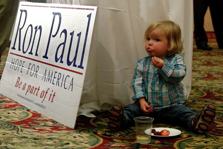 Eisley Collins, 2, snacks next to a Ron Paul sign at a Republican watch party in Oklahoma City, Tues