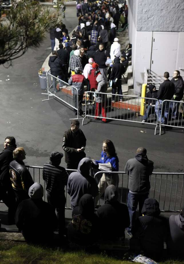 A Best Buy employee hands out paperwork to Black Friday shoppers, queued up behind barricades, as they wait for the opening of the store for Black Friday to begin. Hundreds of shoppers at Best Buy in Pinole, Calif., waited in line (some for days) for the beginning of the holiday shopping season at midnight following Thanksgiving on Thursday, November 24, 2011. (Carlos Avila Gonzalez / The Chronicle)