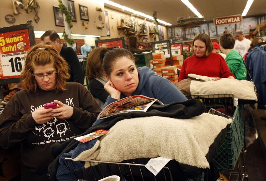 In this Nov. 25, 2011 file photo, Christy Embry, left, and Crystal Coleman wait in a long check out line during the Black Friday sale at Bass Pro Shops, in Memphis, Tenn. (Associated Press)