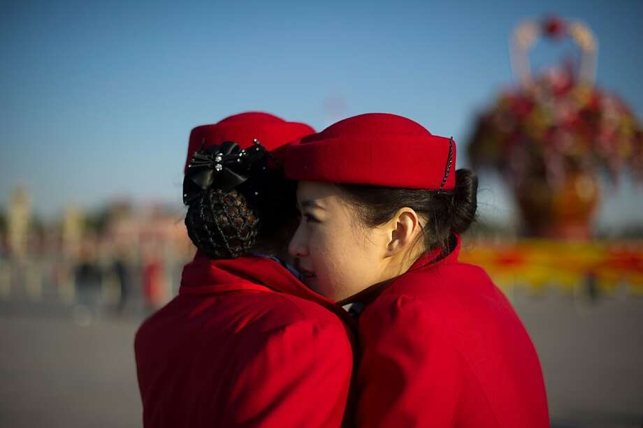 Hostesses embrace against the cold in Beijing's Tiananmen Square as they wait for delegates to arrive at the Great Hall of the People for the closing ceremony of the Communist Party Congress. Photo: Ed Jones, AFP/Getty Images