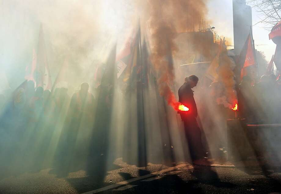 A man holds a flareas thousands of French and Belgians demonstrate during an anti-austerity protest in Lille, France. Trade unions led nationwide strikes and anti-austerity protests across Europe. Photo: Philippe Huguen, AFP/Getty Images