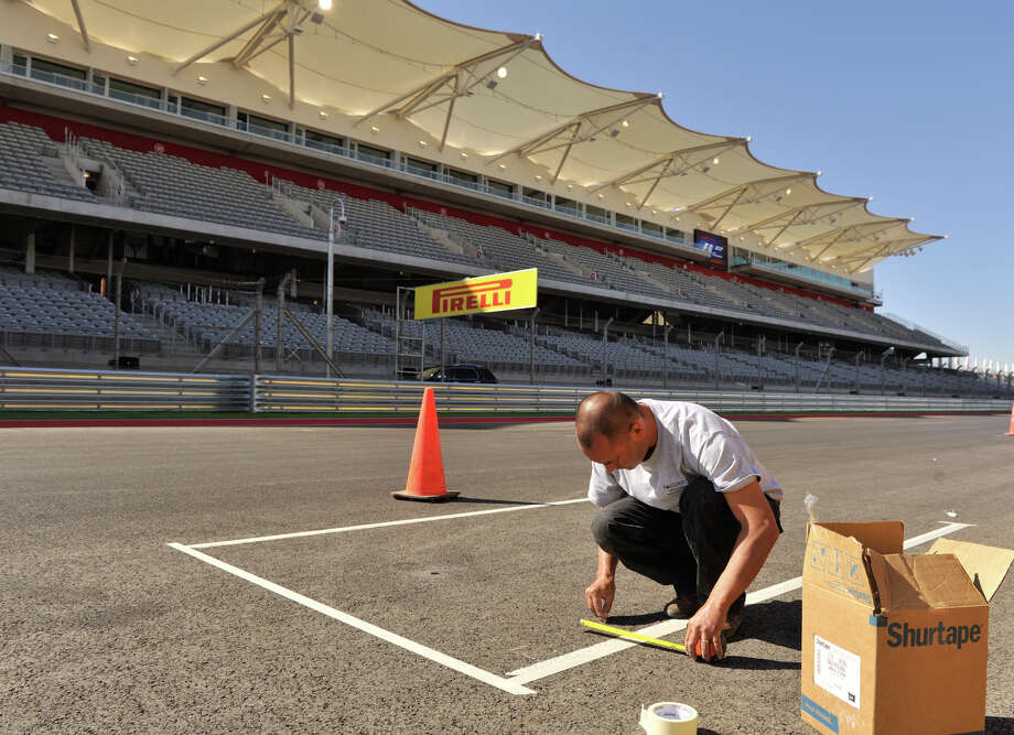 Craig Turnbull of Roadgrip Ltd. gets ready to paint the track starting spots Wednesdy in preparation for Formula 1's United States Grand Prix at Austin's Circuit of the America's on Sunday. San Antonio businessman Red McCombs is a major investor in the facility. Photo: Robin Jerstad/For The Express-Ne