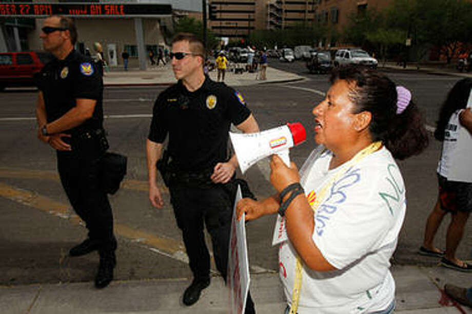 Josephine Nevarez, who opposes the Arizona Immigration Law, stands outside the US district court in Phoenix, Arizona with a bullhorn. (Ross D. Franklin/AP)