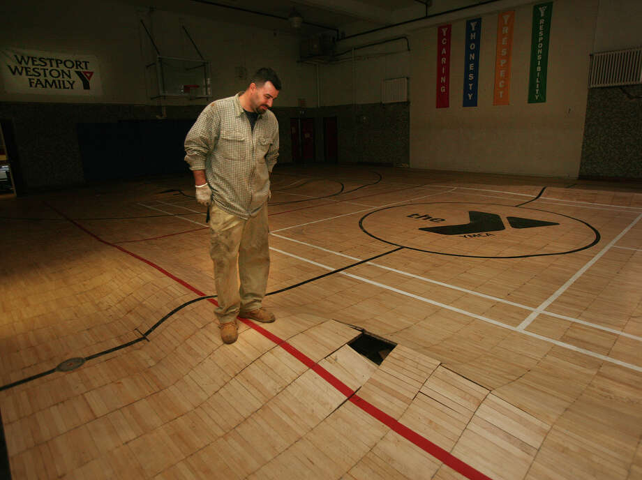 Craig Pietrowicz, an employee of Northeast Generator in Bridgeport, looks at the gym floor destroyed by flooding from Hurricane Sandy in the Westport Weston Family Y in downtown Westport on Wednesday, November 14, 2012. Photo: Brian A. Pounds / Connecticut Post