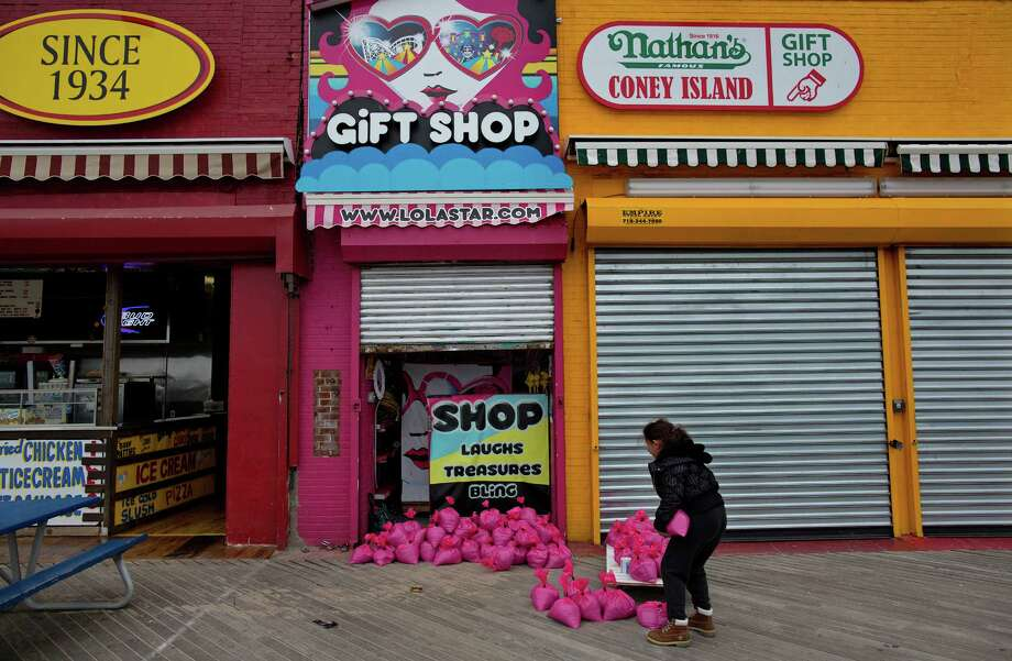 FILE - In this Oct. 28, 2012, file photo, Jessie Rivera, 10, of New York, brings pink sandbags to the door of the shop in New York. Americans cut back sharply on spending at retail businesses in October, an indication that some may still be cautious about the economy. Superstorm Sandy may have slowed business at the end of the month. The Commerce Department said Wednesday, Nov. 14, 2012, that sales dropped 0.3 percent after three months of gains. Auto sales fell 1.5 percent, the most in more than a year. (AP Photo/Craig Ruttle, File) Photo: Craig Ruttle, FRE / FR61802 AP
