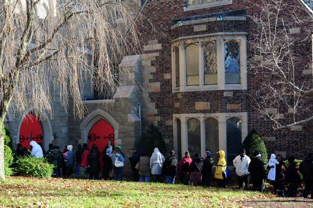 People line up Wednesday, Nov. 14, 2012 outside Golden Hill Church in Bridgeport for the Bridgeport Rescue Mission's Thanksgiving Pantry Bag / Turkey and Coat distribution.  Volunteers will be distributing turkeys and all the fixings along with warm winter coats through Nov. 21, 2012. Photo: Autumn Driscoll / Connecticut Post