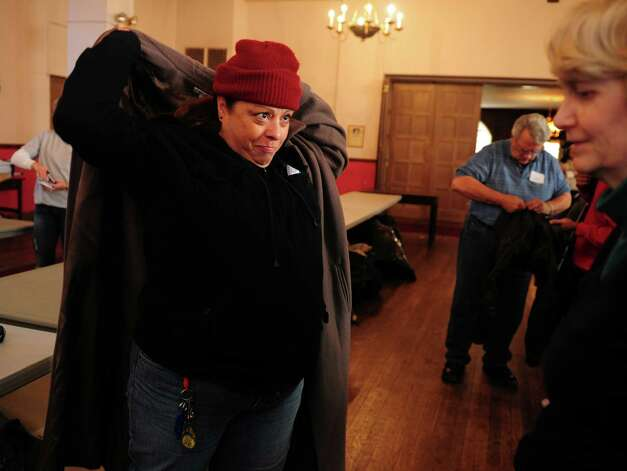 Vilma Ortiz, of Bridgeport, tries on a winter coat Wednesday, Nov. 14, 2012 at Golden Hill Church in Bridgeport during the Bridgeport Rescue Mission's Thanksgiving Pantry Bag / Turkey and Coat distribution.  Volunteers will be distributing turkeys and all the fixings along with warm winter coats through Nov. 21, 2012. Photo: Autumn Driscoll / Connecticut Post