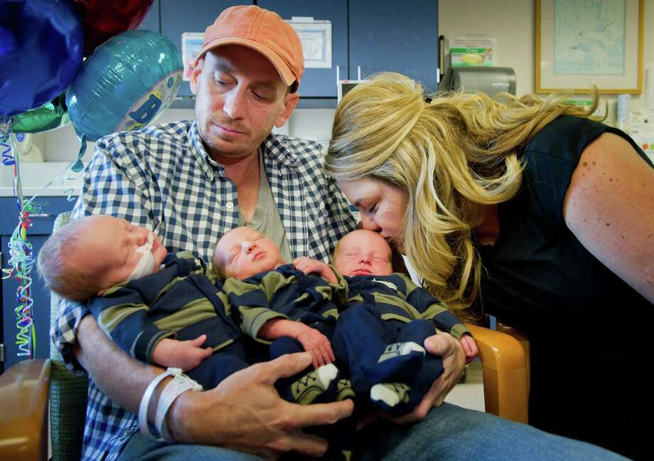 Jason and Brittany Deen appear at a press conference at Sutter Medical Center in Sacramento, California, Wednesday, November 14, 2012 with their triplet sons, from left, Sidney 7.8 lbs, Jenson 5.5 lbs and Elliott, 7.3 lbs. The triplet boys apparently beat the Guinness World Record as the heaviest triplets in the world with a combined weight of 20 pounds at birth. Brittany and Jason Deen's triplets were naturally conceived - a 1 in 8,000 occurrence. With a complication-free pregnancy, Brittany was able to carry the babies almost full-term, a rarity with multiples. Brittany gave birth to the three boys weighing a combined 20 pounds at Sutter Memorial Hospital on November 8. (Manny Crisostomo/Sacramento Bee/MCT) Photo: Manny Crisostomo, McClatchy-Tribune News Service / Sacramento Bee