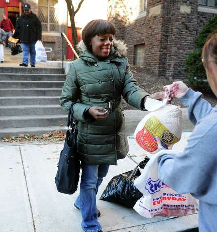 Chrislene Barton, of Bridgeport, recieves a turkey Wednesday, Nov. 14, 2012 outside Golden Hill Church in Bridgeport during the Bridgeport Rescue Mission's Thanksgiving Pantry Bag / Turkey and Coat distribution.  Volunteers will be distributing turkeys and all the fixings along with warm winter coats through Nov. 21, 2012. Photo: Autumn Driscoll / Connecticut Post