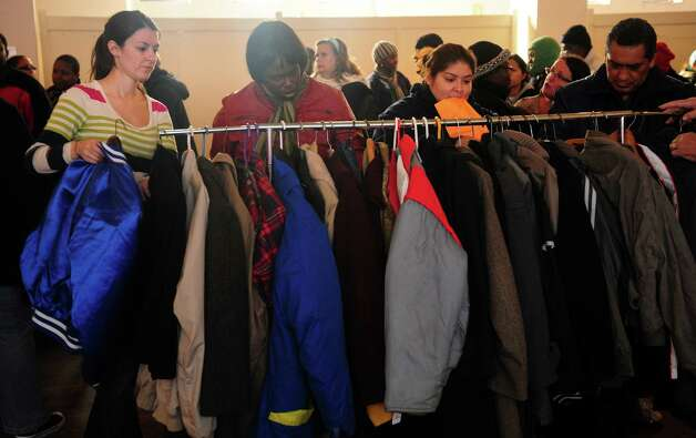 People look for a coat in their size Wednesday, Nov. 14, 2012 at Golden Hill Church in Bridgeport during the Bridgeport Rescue Mission's Thanksgiving Pantry Bag / Turkey and Coat distribution.  Volunteers will be distributing turkeys and all the fixings along with warm winter coats through Nov. 21, 2012. Photo: Autumn Driscoll / Connecticut Post