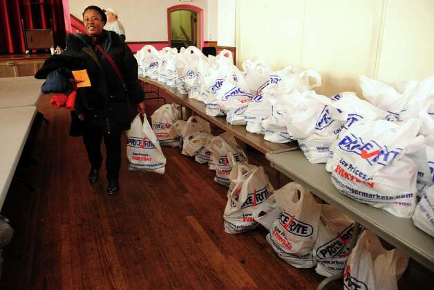 Desirne Henry, of Stratford, walks past hundreds of bags of food Wednesday, Nov. 14, 2012 at Golden Hill Church in Bridgeport during the Bridgeport Rescue Mission's Thanksgiving Pantry Bag / Turkey and Coat distribution.  Volunteers will be distributing turkeys and all the fixings along with warm winter coats through Nov. 21, 2012.  A volunteer estimated the group had at least 400 bags of fixings ready to go. Photo: Autumn Driscoll / Connecticut Post