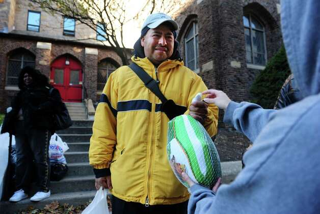 Armondo Crisanto, of Bridgeport, recieves a turkey Wednesday, Nov. 14, 2012 outside Golden Hill Church in Bridgeport during the Bridgeport Rescue Mission's Thanksgiving Pantry Bag / Turkey and Coat distribution.  Volunteers will be distributing turkeys and all the fixings along with warm winter coats through Nov. 21, 2012. Photo: Autumn Driscoll / Connecticut Post