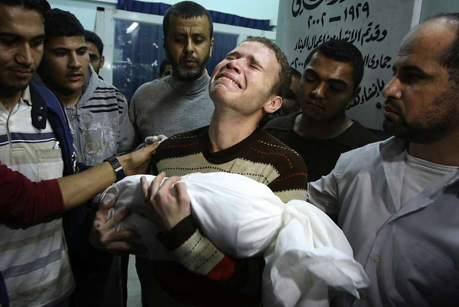 Jihad Masharawi weeps while he holds the body of his 11-month old son Ahmad, at Shifa hospital following an Israeli air strike on their family house, in Gaza City, Wednesday, Nov. 14, 2012. The Israeli military said its assassination of the Hamas military commander Ahmed Jabari, marks the beginning of an operation against Gaza militants. Photo: Majed Hamdan, Associated Press