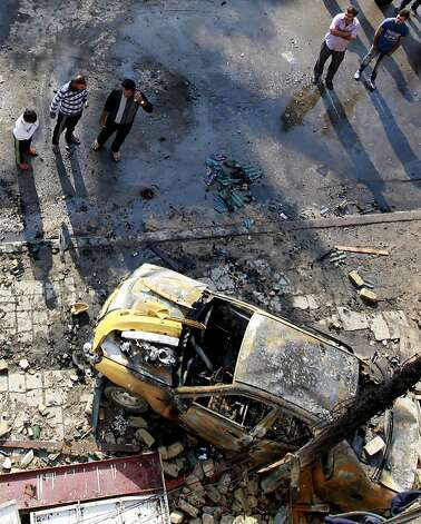 People gather at the scene of a car bomb attack in central Baghdad, Iraq, Wednesday, Nov. 14, 2012. Iraqi insurgents unleashed a new wave of bombings across the country early Wednesday targeting security forces and civilians, killing and wounding scores of people, police said. (AP Photo/Khalid Mohammed) Photo: Khalid Mohammed, Associated Press
