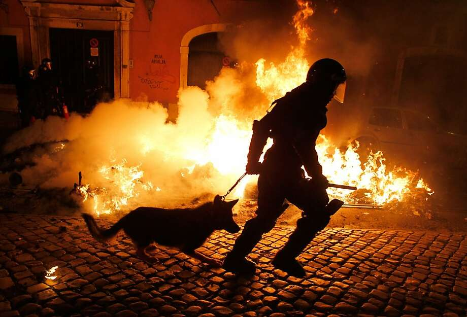 A riot policeman runs past a fire set by protestors during clashes in Lisbon during a general strike Wednesday, Nov. 14 2012. The second general strike in eight months in Portugal, where the government intends to intensify austerity measures next year, left commuters stranded as trains ground to a virtual halt and the Lisbon subway shut down. Photo: Francisco Seco, Associated Press