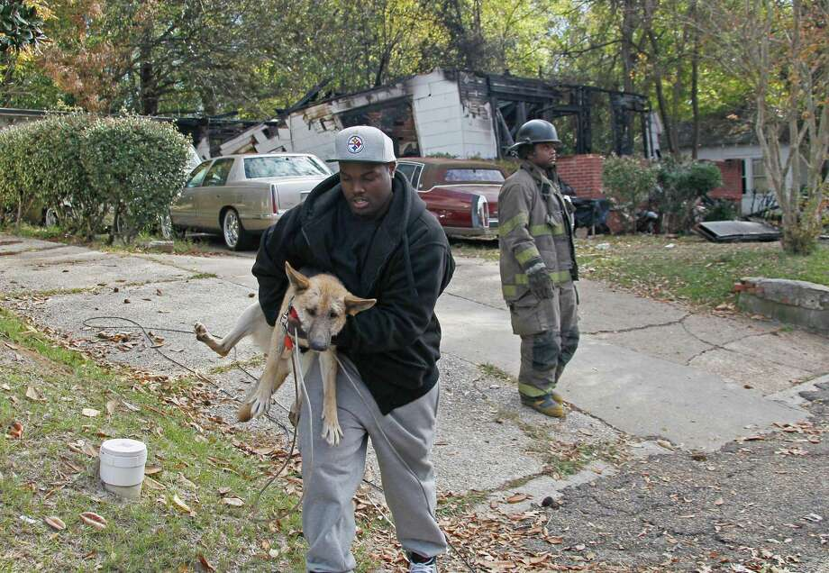 A resident removes one of several dogs from a house that burned when a small plane carrying three people crashed into it Tuesday evening. A woman in the house was injured, and all three aboard the plane died. Photo: Rogelio V. Solis, STF / AP
