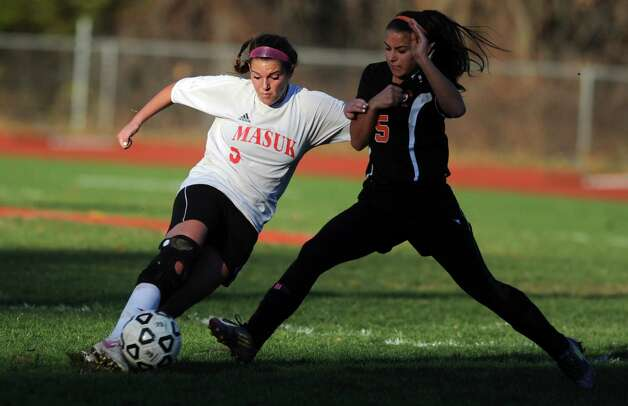 Masuk's Emily Montgomery kicks the ball as Watertown's Olivia Gugliotti moves in to defend during the Class LL quarterfinals Wednesday, Nov. 14, 2012 at Masuk High School in Monroe, Conn. Photo: Autumn Driscoll / Connecticut Post