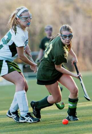 Greenwich Academy's Emilia Tapsall moves the ball past Deerfield Academy's Lucy Baldwin in a NEPSAC (New England Preparatory School Athletic Council) field hockey quarterfinal game played at Greenwich Academy, Greenwich, CT Wednesday November14th 2012. Photo: Mark Conrad / Stamford Advocate Freelance