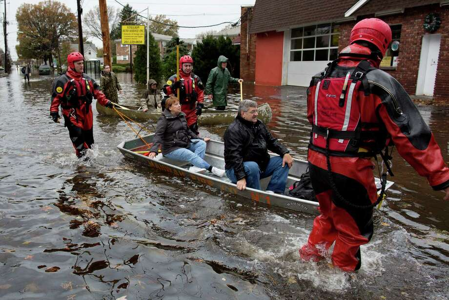 FILE-- In this Tuesday, Oct. 30, 2012 photo, rescuers bring people out by boat in the wake of superstorm Sandy  in Little Ferry, N.J. Despite days of dire forecasts and explicit warnings, hundreds of thousands of people in New York and New Jersey ignored mandatory evacuation orders as Superstorm Sandy closed in. Now, after scores of deaths and harrowing escapes, emergency officials say they will look at what more can be done to persuade residents to get out when their lives are in danger. (AP Photo/Craig Ruttle) Photo: Craig Ruttle, Associated Press / FR61802 AP