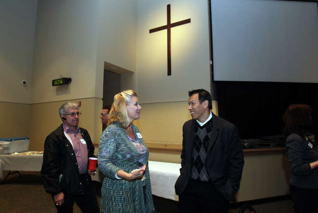 Former Dallas Cowboy and Texas Aggie linebacker Dat Nguyen (right) speaks with Lisa Hurst Tuesday November 13, 2012 after a luncheon held by the Christian Business Chamber of Commerce at Community Bible Church. Nguyen spoke to the group about his faith and his experiences on and off the gridiron. Photo: JOHN DAVENPORT, San Antonio Express-News / ©San Antonio Express-News/Photo Can Be Sold to the Public