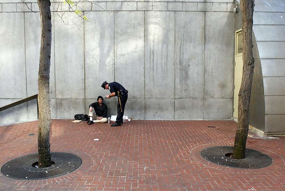 At the Powell Street Station entrance, SFPD Officer James Tacchini cites one of the city's public drinkers. Photo: Carlos Avila Gonzalez, The Chronicle